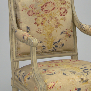 "This set of chairs [2 armchairs, 3 side chairs] is characterized by its flat, rectangular backs and seat frames on fluted supports.  Each chair is topped by an arched crest rail centered with carved, crossed quiver and torch and an acanthus leaf finial at each end.  The chairs' frames are painted gray and white.  Each chair also has a bowed front seat rail, twisted with ribbon banding and molding. Open padded arms terminate in scrolls; acanthus leaf at each knee; quatrefoil rosette in square at front and side corners above each stop-fluted foreleg; ""X"" in square at front and side above each fluted rear leg. Reverse of seat back has vertical splat between crest and seat rails. Chair, armpads and (A) loose seat cushion upholstered in cream brocade with design of red roses and yellow leaves tied with blue and ivory ribbon."