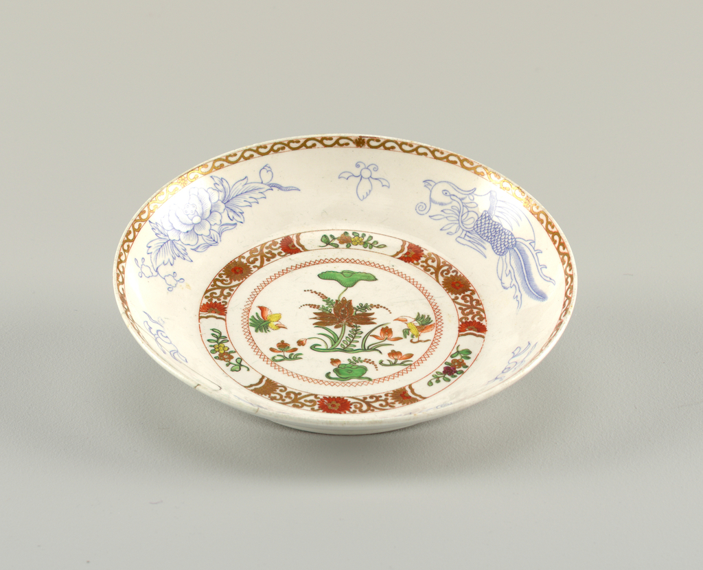 Shallow, curved bowl decorated with polychrome overglaze painting. Scrolled band on edge.