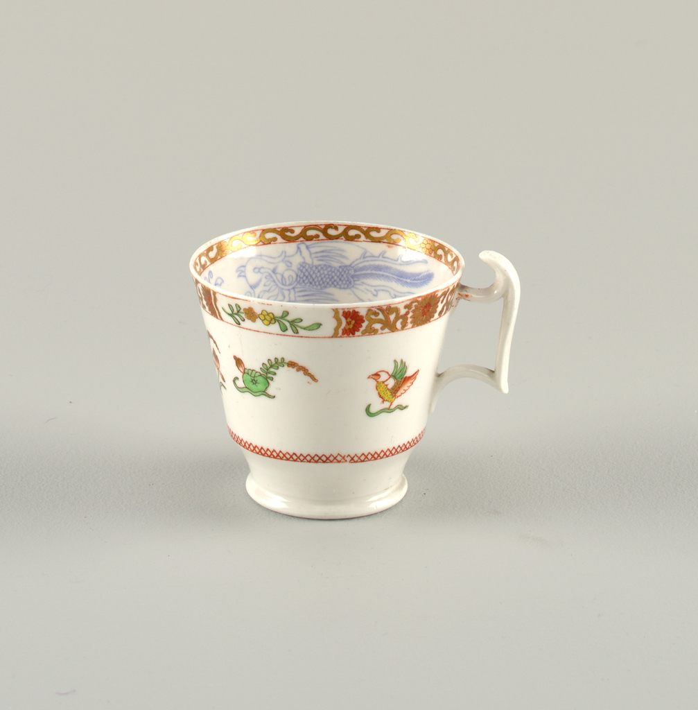 """Flaring cup with straight sides. Narrow, circular feet. Angular handle with 'spur"""". Curved saucer. Inside of cup and edge of saucer decorated with polychrome overglaze painting. Scrolled band on edge."""