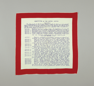 Handkerchief with a red border and blue text with the preamble and amendments to the Constitution.