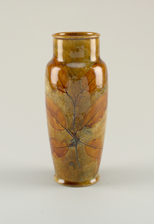 Cylindrical body with molded foot ; body wall curves outward toward high, narrow shoulder, above which is straight-sided short neck. Overall mottled ochre glaze; decoration of impressed leaves on stem at front and back, leaves glazed in clear brown. Glaze continues within lip interior, with run-lines visible.