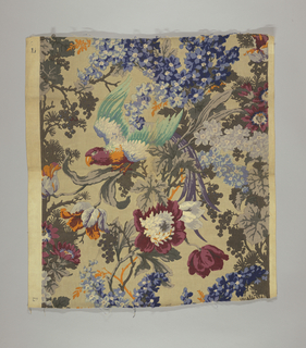"Polychrome block print on tan linen ""cretonne"". Serpentine grey and orange branches with grey and black leaves. Flowering garlands: two shades of dark blue, two shades of light blue, two shades of grey. Growing from branches are large maroon flowers and large lavender and orange flowers. In midst of flora is a large parrot with a maroon head, blue and green wings. Side repeat is completed by matching selvages side to side at a one-half drop repeat."