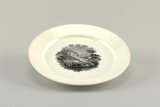 White plate with central transfer-printed decoration showing a town in a mountainous landscape.