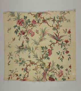 Polychrome block print on pale yellow linen. Serpentine flowering branches, mostly red and pink flowers. In the branches many brilliantly colored exotic birds — green, red, blue, and yellow. Multicolored butterflies fly among branches.