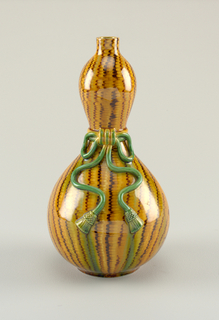 Double gourd vase with vertical yellow and brown stripes. At center, relief molded bow knot with tassels.