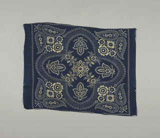 Blue handkerchief printed with a design of white flowers, leaves and dots.