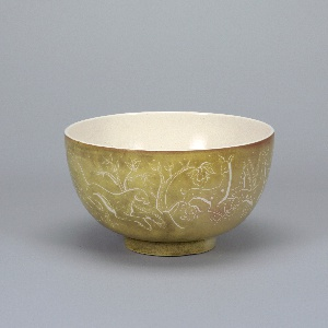 Large, round, deep bowl of heavy ware on inch-high foot. Outside: mottled greyed-green with tinges of pink, crackled glaze with decoration in reserved white lines depicting chase through trees and foliage of rabbit, leopard, deer, bird, boars, and a bull. Interior: crackled white glaze.