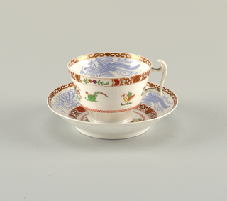 "Flaring cup with straight sides. Narrow, circular feet. Angular handle with 'spur"". Curved saucer. Inside of cup and edge of saucer decorated with polychrome overglaze painting. Scrolled band on edge."