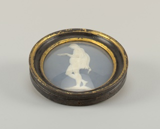 Vertical oval plaque, pale blue solid jasper body with darker slip and white relief showing a youth, nude except for drapery falling from shoulder. He stands in left profile and hold bowl in one hand. In black and gilt frame.