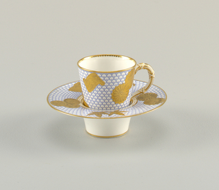 Cup and saucer in white with blue and gold decorative pattern. Saucer appears to have a cylindrical raised foot, where the cup fits into.