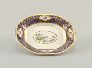 Octagonal dish, border decorated with geometric designs in gold, blue and white. Four medallions, each containing a single pink rose. Bottom decorated with a landscape in an oval bound with ivy.