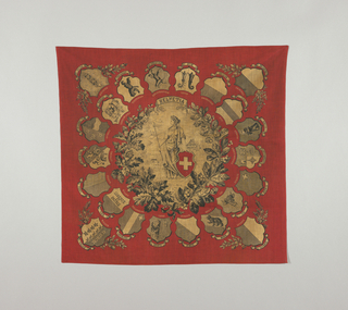 Handkerchief in red and black showing the Swiss female national figure of Helvetia in the center. She holds a spear and a shield emblazoned with the Swiss flag and stands in a bucolic landscape of mountains and chalet-like buildings. A wreath of leaves, acorns and berries surrounds her. In an outer ring are badges bearing cantons of Switzerland with their names in French and German. In the four corners are badges for Lucerne, Valais, St. Gall and Fribourg.