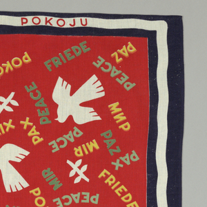 """The field contains white doves, white leaves and the word """"peace"""" in various languages in green, light green or yellow on a red background. Simple slightly waved white band on blue used as a banner on four sides. Inscription in top and bottom border."""