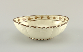 Elliptical dish with lobed sides and exterior molded to resemble basketwork. Brown touches on basketwork edging at top and on foot. Grown grape border about edges on inside.