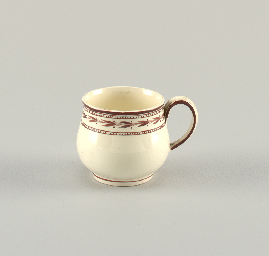 Cup that tapers toward lips. Short foot. Band of overglaze brown decoration at rim, with line at foot and handle.