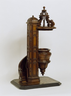 with central column around which a bombe spiral staircase rotates terminating in a similarly curved inverted cone form standing area of the pulpit surmounted by a carved scroll canopy attached above to the column, all resting a rectangular geometrically inlaid marquetry floor-base
