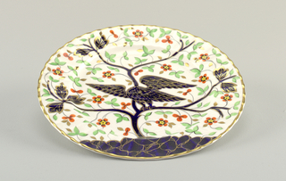 decorated dinner plate with fluted rim, depicting an American eagle with outstretched wings in dark blue with gold definition, perched on flowering tree.