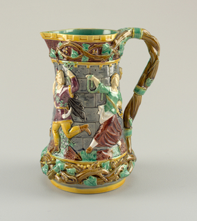 Tall pitcher. Exterior molded with relief figures of a twisted branch at base, surmounted by relief figured (two make, two female) in medieval dress, against simulated stone wall of a tower. Upper portion with branches. Handle formed of twisted ivy branch. All glazed in polychrome.