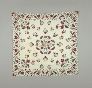 Square of white cotton has scalloped edges that are buttonhole stitched all around. Printed in red, blue and taupe with a central floral motif, scattered small sprays with larger sprays in each corner and curving floral border.