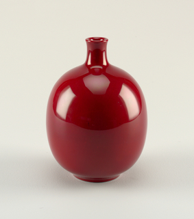 "Balloon-shaped body, slender neck with slight lip. deep red glaze imitating Doulton ""Rouge Flambe""."