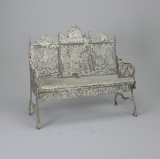 Iron bench for three people painted white. Heart-shaped pattern on apron. Scrolling and crowned backrest.