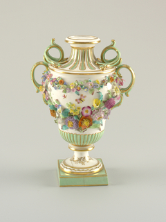 On a square pedestal, a footed pyriform urn, reeding on its lower portion and fluted on contracting neck. Body covered with garlands of applied flowers. Triple-scrolled handles, green and gold. Flowers are polychrome on a white body.