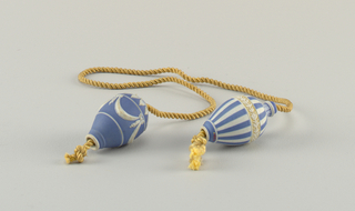 Blue and white jasperware baluster shapes, pierced longitudinally for passage of cord. Dipped jasperware, decorated with row of lancette leaves and four bows connected with swags. Yellow silk cord.