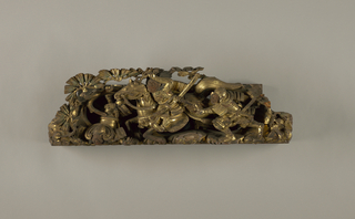 Deep wood carving, two sections of wood riveted together, one section forming the back. Polychromed and gold-lacquered. A scene in a battle between the Heike and the Genji: three Japanese warriors, one mounted on a horse, one running and one fallen; pine branches spreading above.