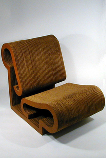 Wide, curved, open-form lounge chair made of laminated shaped strips of corrugated cardboard; masonite layer on left and right sides. Seat and back are formed by the edges of layered cardboard strips; rectangular base.