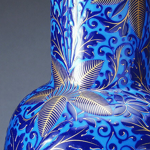 A blue porcelain vase with gold details. Vase is decorated with a pattern of large leaves in the form of stars. The stacked foot and beaded lip are both finished in gold.