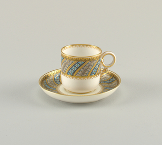 Tea cup with straight sides and loop handle. Cup and saucer decorated with spiraling bands of conventionalized florals and geometric gilding.