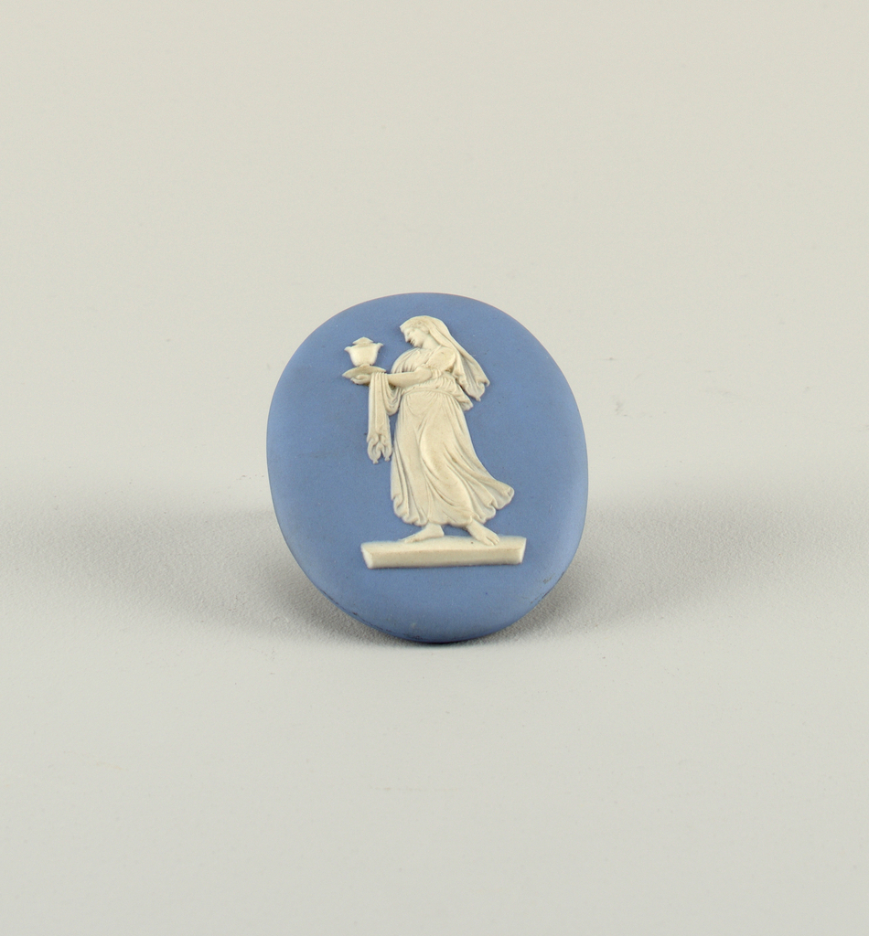 """Oval, white on blue. Full length figure of a woman in classical costume turned three-fourths to the left, head in profile, carrying urn. One of figures from group """"Floral Sacrifice #2"""" in Wedgwood catalog 738 W 393 a pamphlet (musuem library)."""