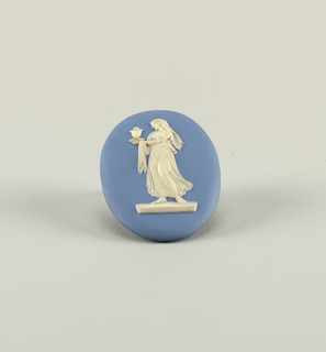 "Oval, white on blue. Full length figure of a woman in classical costume turned three-fourths to the left, head in profile, carrying urn. One of figures from group ""Floral Sacrifice #2"" in Wedgwood catalog 738 W 393 a pamphlet (musuem library)."