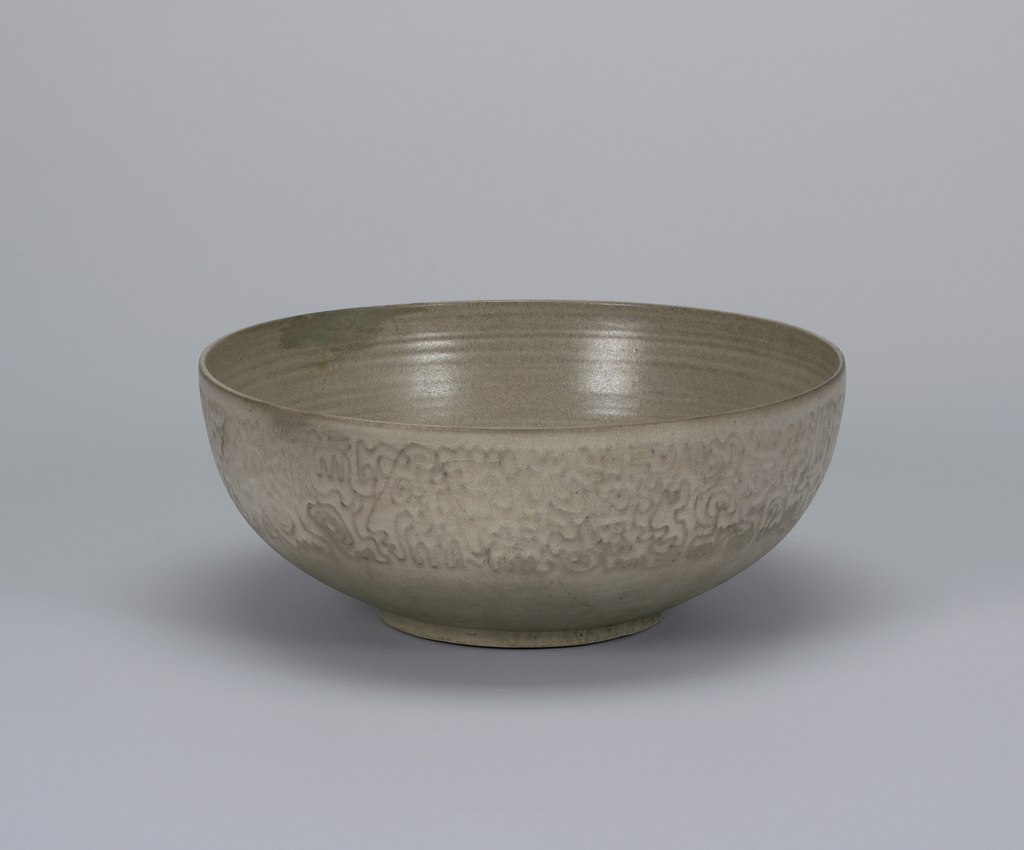 Wide-mouthed bowl on short circular foot; exterior in white with wide molded band of biomorphic designs below rim; interior glazed with gray horizontal striations.