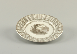 Plate with brown transfer print. Center shows figures in a landscape, within a ring of thistles. Border shows tartan with dots.