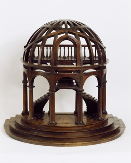 The double staircase spiralling into a single central staircase that gives out onto a balcony with turned balusters supporting a railing, all below a domed top composed of openwork joined wood strips with open arch raised on turned columns from a stepped base with criss-cross openwork strips arranged to form a demi-lune platform