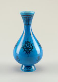 Circular mouth tapering into slender neck flaring to oval body on slightly flaring circular foot.  Glazed deep turquoise with black arabesque decoration.