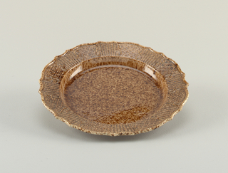 Brown agate ware. Simple molded edge, marly decorated with alternating areas of diapering and basket-work, set apart by scrolls.