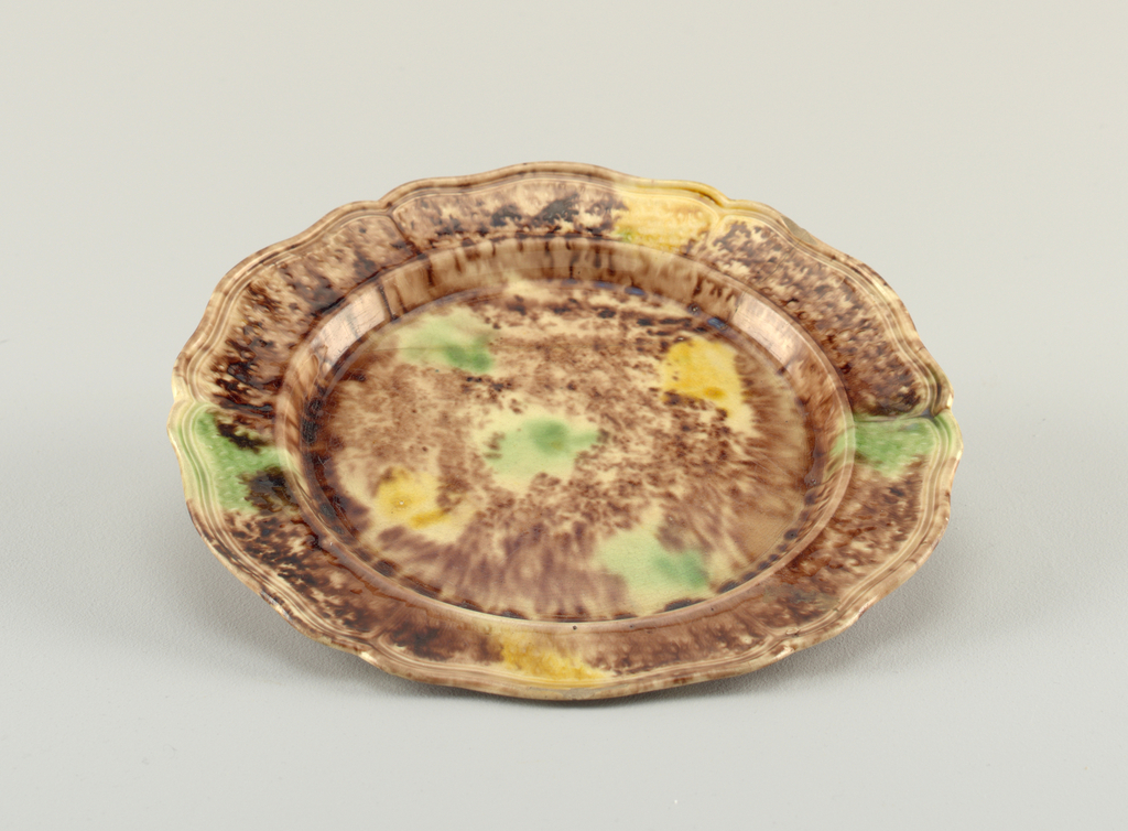 "Molded edge; marly decorated with wavy lines enclosing lozenges, in slight relief. Polychrome ""tortoiseshell"" decoration in brown, with green and yellow blotches on upper surface. Glaze crackling."