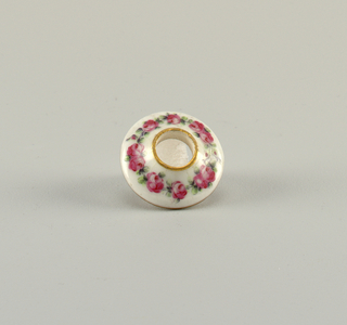 Knob is a flattened sphere; escutcheon circular with ogee profile. Florals, bird and gilding.