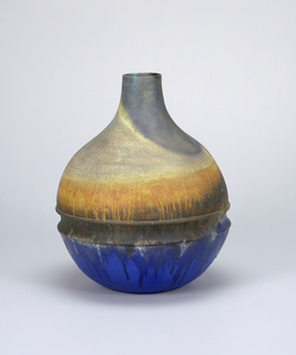 A globous base with a short, narrow neck. A groove the center of the body. Below ridge is blue glaze, above is orange and white.