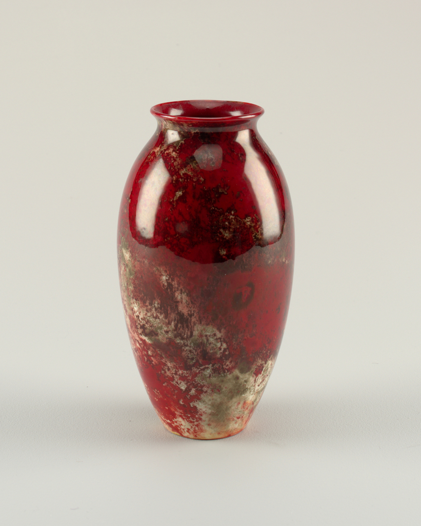 Elongated ovid vase having wide mouth with out-flaring lip. Flambe glaze: reds predominantly, mottled with greys and white.