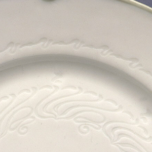 """Molded plate is circular with broad rim. Rim punctuated by 4 indentations and a knot-like device creating a scalloped profile, alternating with four """"v"""" shaped devices. This motif is picked out in soft underglaze green. Center of plate molded with stylized tendril-like motif, and encircled by continuous scroll band, all molded in relief."""