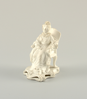 Figure of Hannah More seated on a chair and wearing a bonnet and shawl over her dress, in her right hand she holds a scent bottle, set on a scroll moulded base.
