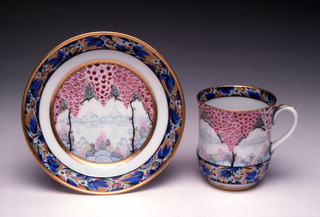 Cup of cylindrical form with rounded base, loop handle; saucer round with flat bottom, raised edge. Both painted with imaginary landscape motifs in reds, blues, gilding