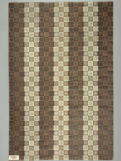 Brown and white checkerboard pattern with small sun and star-shaped motifs inside each square and dark vertical stripes.