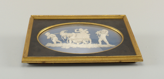 Horizontal oval plaque of solid blue jasperware, with darker blue slip and white relief, showing three putti pulling and coaxing a goat. A fourth putto carries grapes. Oblong black and gilt wooden frame with cut-out oval set with glass.