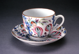 Cup with swelling shape, loop handle; saucer round, slightly raised towardsedges. Cup painted with polychrome loose stylized floral and leaf pattern around sides, thin gilded bands upper and lower edges. Saucer painted withsame pattern, bordered by thin gilded bands; center unpainted.