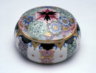 Squat, circular in shape, lid slightly domed; painted with polychrome and gilded stylized floral ornamentation