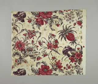 Cream white cotton, block printed in large scale naturalistic flower design in all-over clusters; iris, lily, amaryllis, daffodil and pineapple. Shades of red, dark purple, brown, blue; remains of yellow, now faded, show in sections of leaves, indicating combining of yellow over blue for green. A background printing of fine small scale foliage, in shadow effect, light brown.
